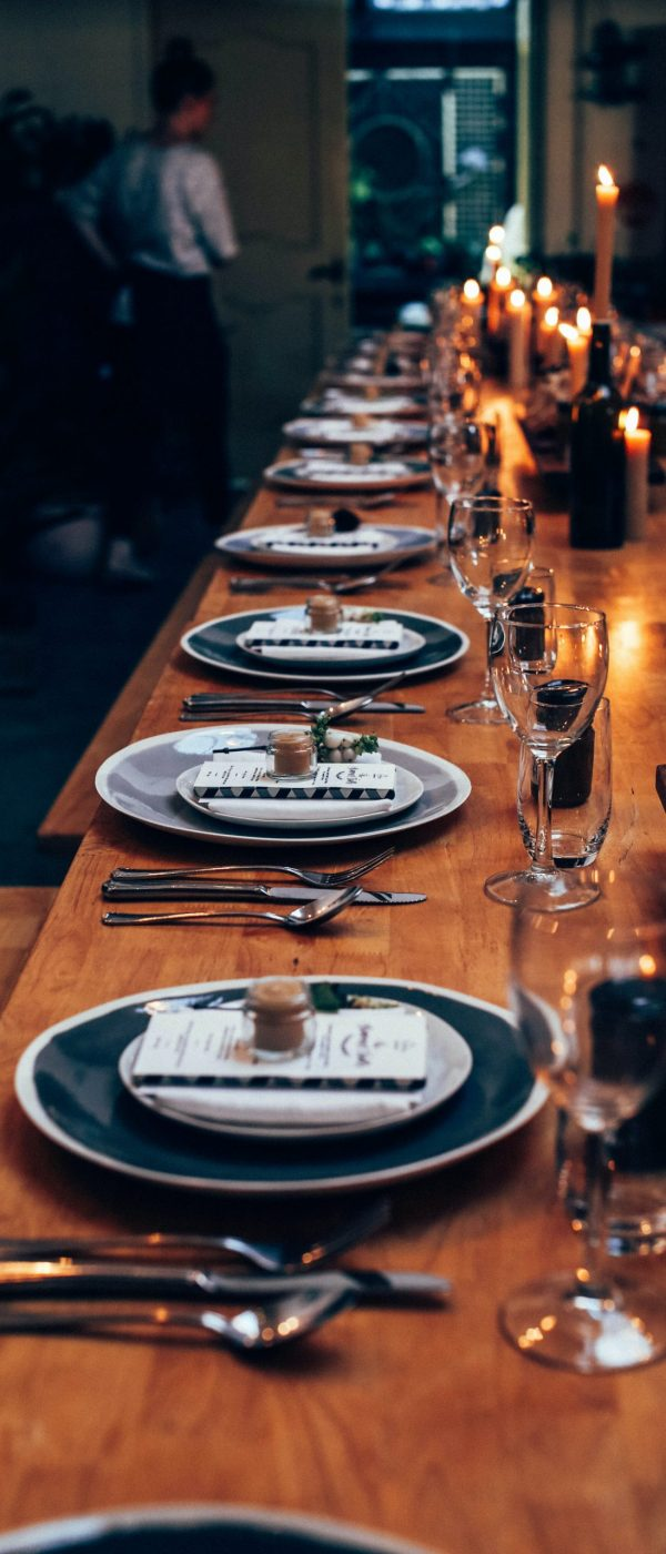 Long wooden table with multiple place settings